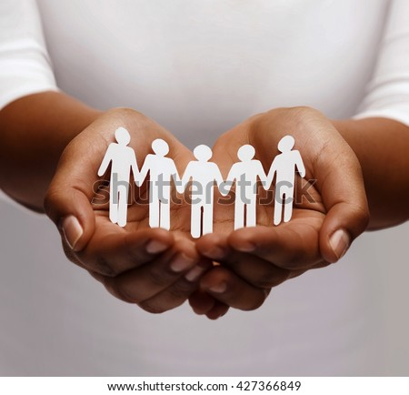 community, unity and charity concept - african american female hands holding and showing paper people team - stock photo