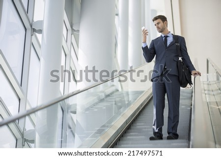 Commuter in the metro station using mobile phone - stock photo
