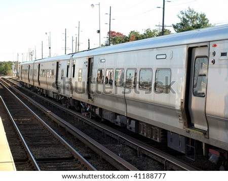 Commuter railroad coming into a station - stock photo