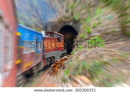 Commuter train carried by obsolete diesel powered locomotive while entering tunnel in Sri Lankan hill region. Radial blurred motion effect applied. Concept of traveling mode in Asian countries. - stock photo