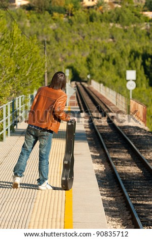Commuter with a guitar waiting for the train - stock photo