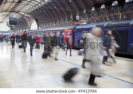 Commuters at Paddington station blurred with slow shutter speed, with all logos removed and all faces blurred beyond recognition. - stock photo