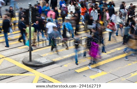 Commuters crossing a busy crosswalk in Hong Kong