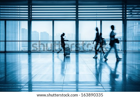 commuters motion blurred with modern corridor in railway station - stock photo