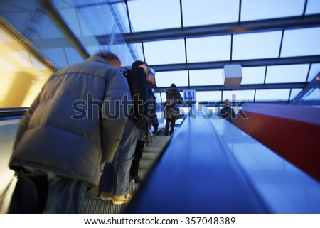 Commuters on escalator at subway station - stock photo