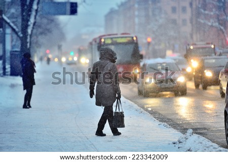 Commuters waiting for arriving bus in snowstorm - stock photo
