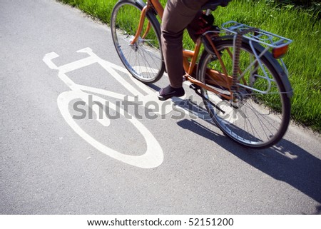 Commuting to work, Blurred woman riding bicycle on a bike path