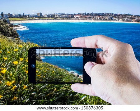 Compact digital camera with view of the beach. - stock photo