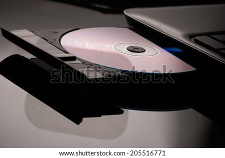 Compact disc drive with on black black background - stock photo