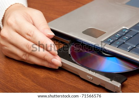 Compact disc on laptop drive - stock photo