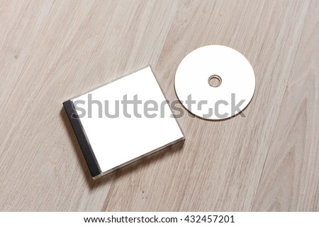 Compact disc template with plastic box with white isolated blank for branding design. CD jewel case mock up with clean free space with booklet for print on wooden table. Perspective view - stock photo