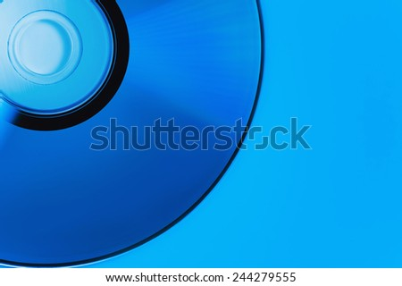 compact disk on blue backgrounds. This colour not computer effect. It is dark blue illumination lamp. Soft focus - stock photo