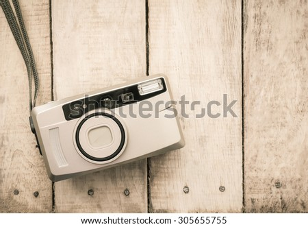 compact film camera on wooden background - stock photo