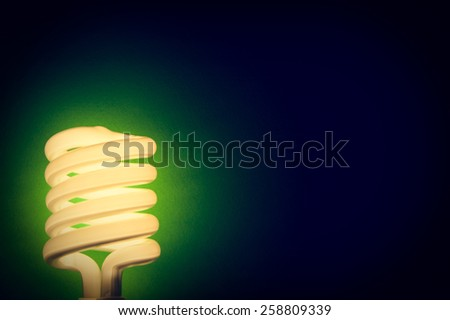 Compact fluorescent energy efficient light bulb turned on with vignette effect - stock photo