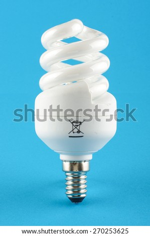 Compact fluorescent energy saving light bulb isolated on the blue background - stock photo