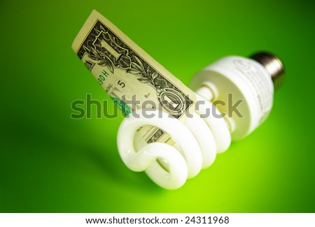 Compact fluorescent light bulb, with a dollar bill - stock photo