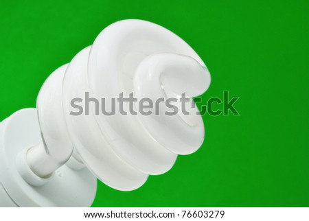 compact fluorescent light (CFL) with green background - stock photo