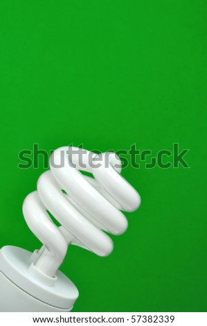compact fluorescent light (CFL) with green background, vertical - stock photo