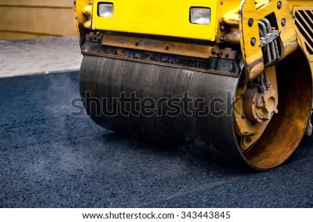 Compact steamroller flatten out the asphalt. - stock photo