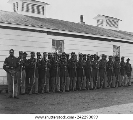 Company E, 4th U.S. Colored Infantry, were part of the defending forces of Washington, D.C. Photo shows two rows of African Americans holding rifles at Fort Lincoln in 1864. - stock photo