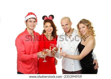 company enjoys Christmas.  Portrait of modern young people enjoying themselves at Christmas party. Company of friends in Santa caps holding flutes of champagne in hands - stock photo