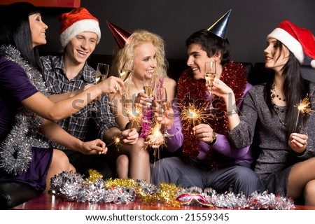 Company of attractive people having fun on Christmas night - stock photo