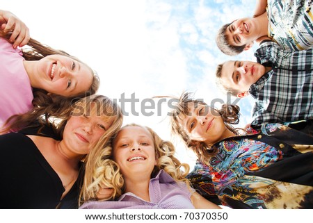 Company of excited teens hugging - stock photo