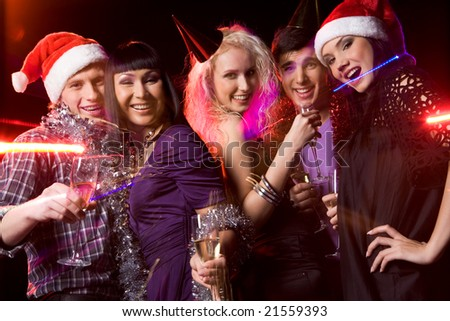 Company of friends clubbing at disco with flutes of champagne in hands - stock photo
