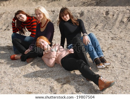 Company of girls resting on the beach sand