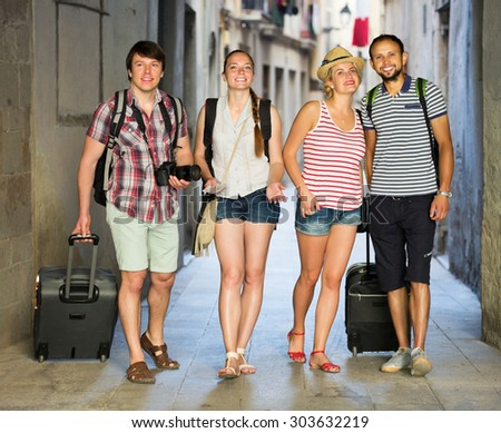 Company of happy travelers with travel bags walking the city - stock photo