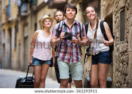 Company of positive active travelers with travel bags walking the city - stock photo