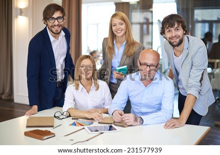 Company of smart employees looking at camera in office - stock photo