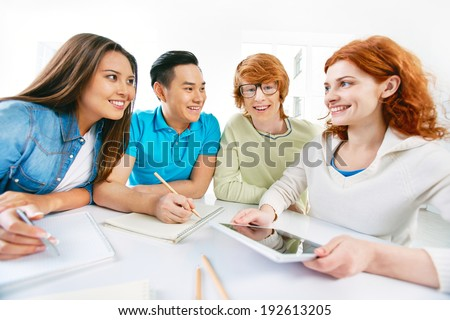 Company of smart groupmates sitting by the table and interacting - stock photo