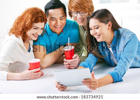 Company of smart groupmates using touchpad while having drink - stock photo