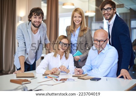 Company of successful business partners looking at camera in office - stock photo