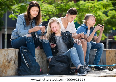 Company of yonug teenagers sitting and looking at their mobile phones in park