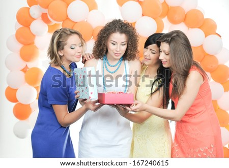 Company of young beautiful cheerful girlfriends celebrate birthday and are photographed