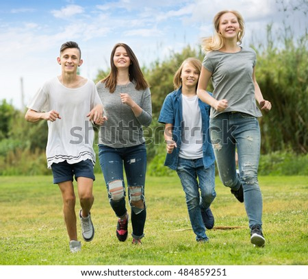 Company of young friends running in park on summer