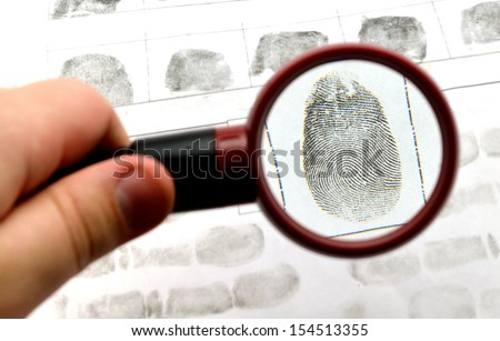 comparing the fingerprint through the dactyloscopic magnifier glass - stock photo