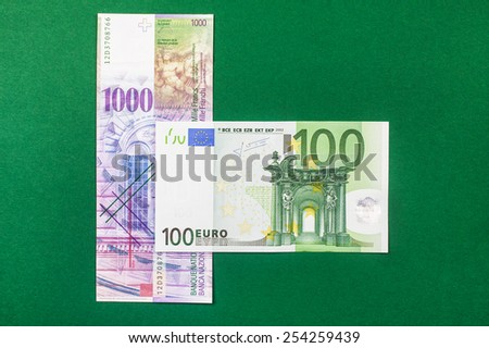 comparison of Swiss francs and euros on green background - stock photo