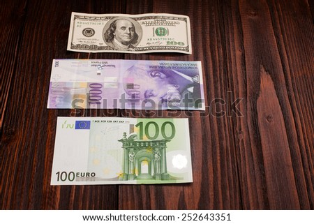 comparison of Swiss francs dollars and euros on wooden table - stock photo