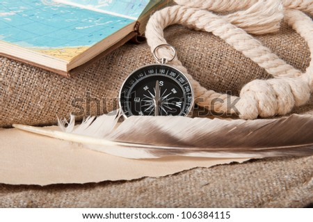 compass and a map of the rope on a light background - stock photo