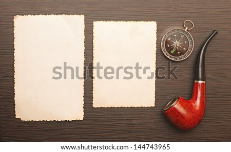 Compass and a pipe with a old photo frame on wooden background - stock photo