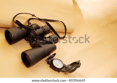 Compass and binoculars on ancient parchment paper - stock photo