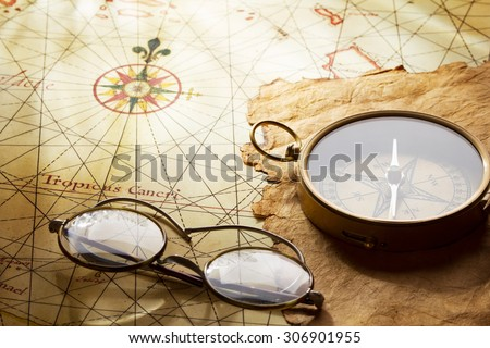 "Compass and glasses on antique map. The map of West Indies dated the end of 1600 yy , contains text in latin ""Tropicus Cancri"" which means The Tropic of Cancer (Northern Tropic)"