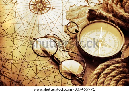 "Compass and glasses on antique map. The map of West Indies dated the end of 1600 yy , contains text in latin ""Tropicus Cancri"" which means The Tropic of Cancer (Northern Tropic) - stock photo"