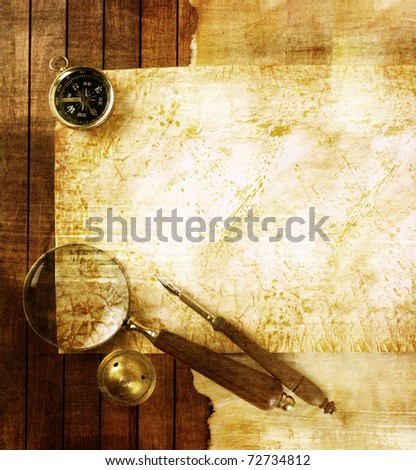 Compass and magnifier on textured paper - stock photo