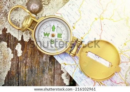 Compass and map on the wooden background - stock photo