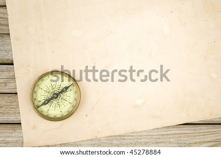 compass and old paper on wood background - stock photo
