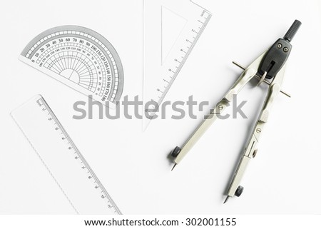 Compass and other measuring equipment on white paper